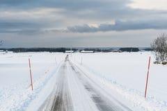 Route de campagne avec des enjeux de neige photographie stock libre de droits