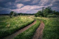 Route de campagne d'enroulement dans la soirée nuageuse Images stock