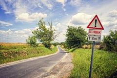 Route de campagne d'enroulement et un poteau indicateur photographie stock libre de droits