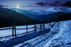 Route de campagne dedans aux montagnes d'hiver la nuit photos stock