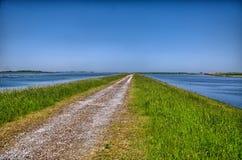 Route de campagne entourée par l'eau en Hollande, Pays-Bas, HDR images libres de droits