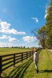 Route de campagne de marche de femme le long des fermes de cheval photographie stock
