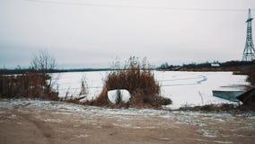 Route de campagne menant pour jeter un pont sur au milieu de la rivière congelée couvert dans la neige banque de vidéos