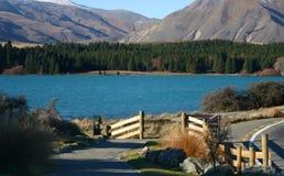 Route de campagne pittoresque avec les barrières en bois, l'eau bleue profonde, la forêt éloignée et les montagnes images stock