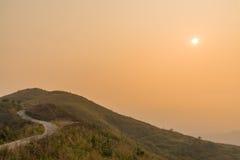 Route de courbe au-dessus de la colline au coucher du soleil Images stock