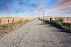 Route de désert par la ferme de turbines de vent sur des collines de la Californie Images libres de droits