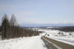 Route de l'hiver aux collines des montagnes de Sayan. Image libre de droits