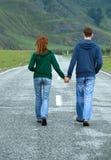 Route de marche de jeunes couples Images libres de droits