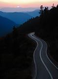 Route de montagne au coucher du soleil Photographie stock libre de droits