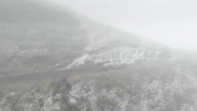 Route de montagne en Géorgie allant au passage en mauvais temps dans le brouillard et la neige banque de vidéos