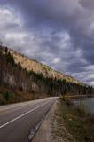 Route de montagne sous un ciel nuageux Photographie stock libre de droits