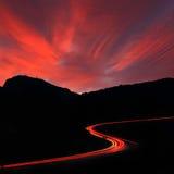 Route de nuit contre le coucher du soleil Photo stock