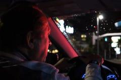 Route de nuit Vue de l'intérieur de voiture Lumière normale l'homme conduisant une voiture la nuit dans le visage reflète la coul image libre de droits