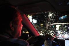 Route de nuit Vue de l'intérieur de voiture Lumière normale l'homme conduisant une voiture la nuit dans le visage reflète la coul photographie stock libre de droits