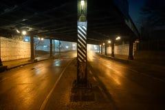 Route de rue et pont urbains sombres et graveleux de vintage la nuit photos stock