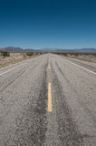 Route 66. In the depths of the mojave desert in Arizona,  the famous American Mother Road Route 66 stretches for forever into the diminishing distance. Big blue Stock Images