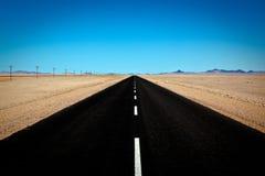 Route devant le ciel bleu et le mountai Photographie stock libre de droits