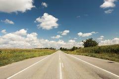 Route droite par des champs dans le jour ensoleillé avec le ciel bleu nuageux, horizontal Images stock