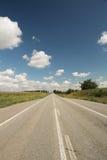 Route droite par des champs dans le jour ensoleillé avec le ciel bleu nuageux, vertical Image libre de droits