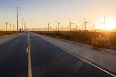 Route droite par le champ d'éoliennes au coucher du soleil Image stock