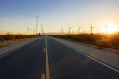 Route droite par le champ d'éoliennes au coucher du soleil Photos libres de droits