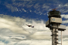 The route is the earth-sky. Passenger aircraft takes off against the background of the cloudy sky and the flight control tower at Royalty Free Stock Photo
