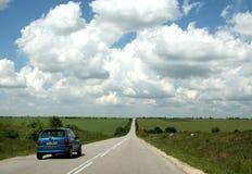 Route ensoleillée avec beaucoup de nuages Image libre de droits