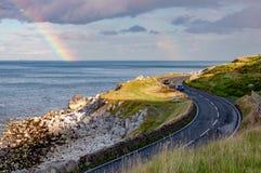 Route et arc-en-ciel côtiers d'Antrim en Irlande du Nord, R-U photographie stock libre de droits