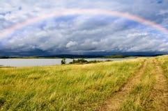 Route et arc-en-ciel de zone au-dessus de lac Photographie stock libre de droits