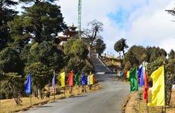 Route et escaliers décorés des drapeaux colorés au monastère de Druk Wangyel du passage de Dochula au Bhutan image libre de droits