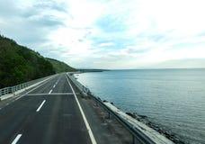 Route et océan avec la montagne, la vue ou le fond Image stock