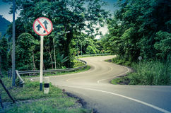 Route et panneau d'avertissement incurvés par serpent Photo libre de droits