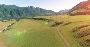 Route et pré ruraux aériens de montagne au matin ensoleillé d'été Route et rivière d'asphalte banque de vidéos