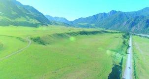 Route et pré ruraux aériens de montagne au matin ensoleillé d'été Route et rivière d'asphalte clips vidéos