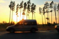 Route et voiture brouillées contre le contexte du coucher du soleil et des arbres, mouvement de vitesse Images stock