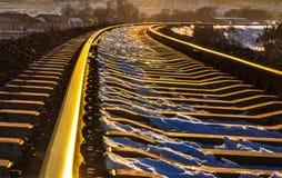 Route ferroviaire d'or dans le village d'hiver Image libre de droits