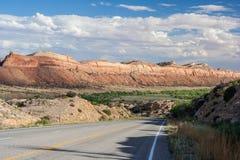 Route fonctionnant par des canyons du monument national le Colorado Etats-Unis d'ancients Photographie stock libre de droits