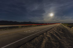 Route 66 with Full Moon and Streaking Train. Route 66 sign with full moon and streaking train in the California Mojave desert Royalty Free Stock Photography