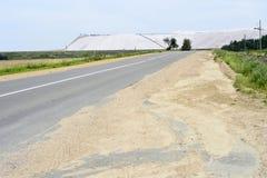 Route goudronnée au bord des décharges des mines du Belarus, la ville de Soligorsk Photographie stock libre de droits