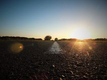 Route goudronnée au coucher du soleil Photographie stock libre de droits