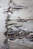 Route goudronnée cassée de trottoir et de nid de poule après l'hiver. Photo stock