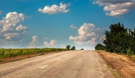 Route goudronnée de mère patrie partant dans le ciel avec des nuages Photographie stock libre de droits