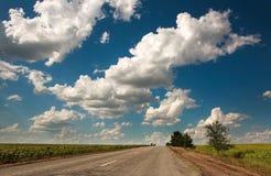 Route goudronnée de mère patrie partant dans le ciel avec des nuages Images stock