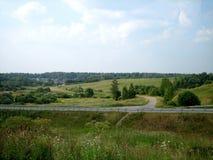 Route goudronnée directe par la campagne sous le ciel, sur lequel les nuages flottent photos libres de droits