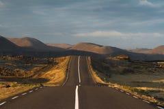 Route goudronnée droite et vide allant au-dessus des collines Images stock
