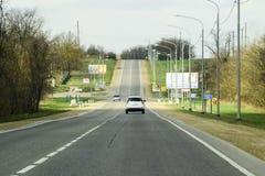 Route goudronnée en avant de la voiture et montée au mamelon Images libres de droits