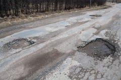 Route goudronnée endommagée après l'hiver. photographie stock