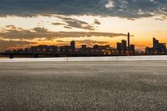 Route goudronnée et horizon moderne de ville au coucher du soleil photographie stock libre de droits