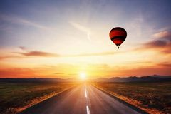 Route goudronnée le long et boule colorée dans le ciel au coucher du soleil photos libres de droits