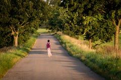 Route goudronnée menant parmi des arbres Au milieu de la route solitaire Image stock